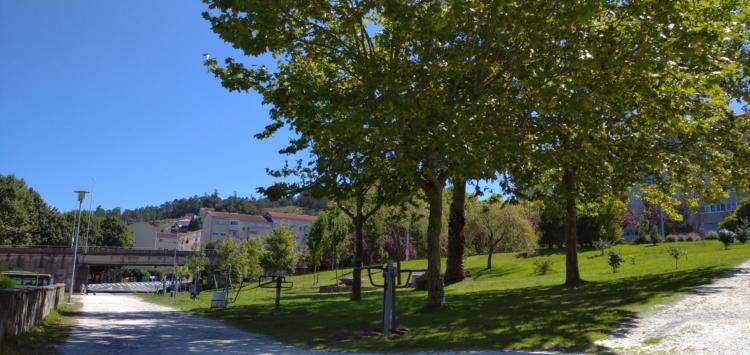 Máquinas de deporte a disposición dos usuarios do parque, con dous dos sendeiros que atravesan o parque e as árbores que dan sombra ás máquinas en primeiro plano