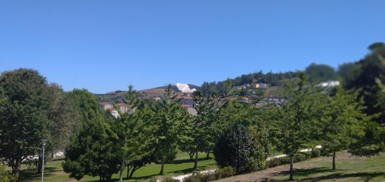 A Cidade da Cultura vista desde as ladeiras do parque do Restollal, con unha sendera do Restollal e o seu arboredo en primeiro plano